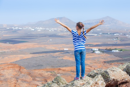 girl standing on cliffs edge, looking to a sky  photo