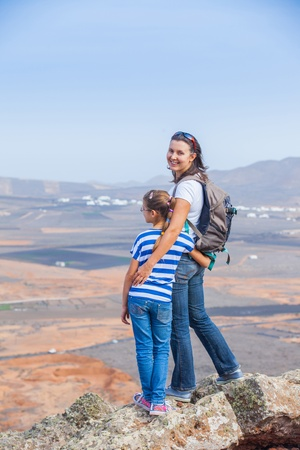 Mother and daughter standing on cliffs edge photo