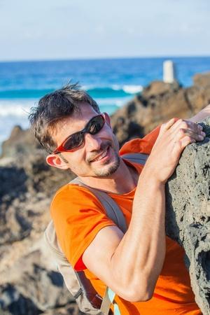 rockclimb: Young man climbing indoor wall. Backround sea