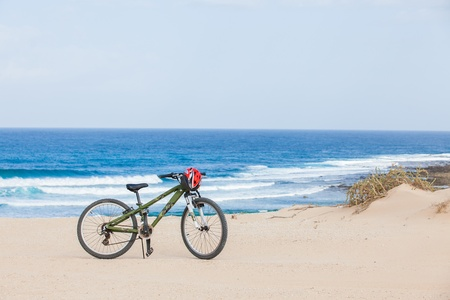 Bicycle with helmet, stand on the beach. photo