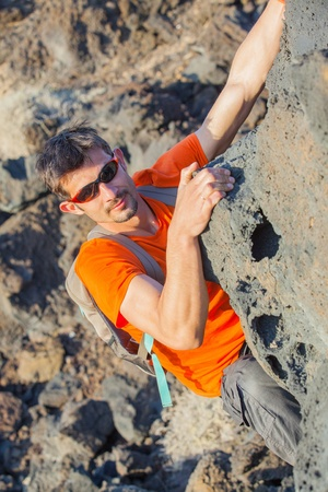 Young man in glasses with backpack climbing photo