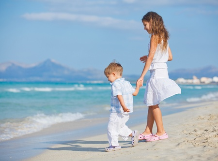 children playing together: Young girl and boy playing happily at pretty beach