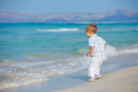 Young cute boy playing happily at pretty beach photo