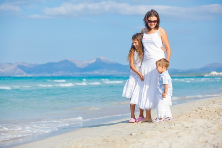 Young mother with her two kids on beach vacation photo