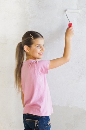 Happy girl painting a wall photo