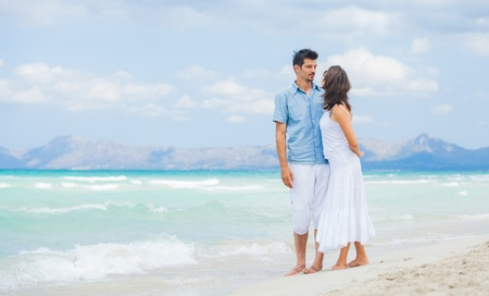 Happy young couple walking on beach photo