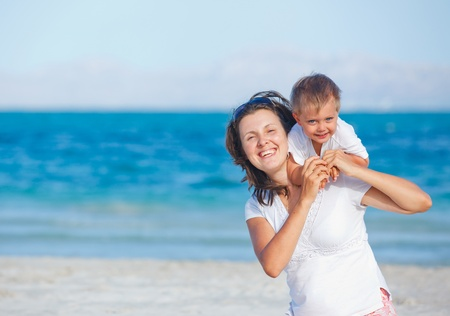 Young mother and her son playing at beach photo