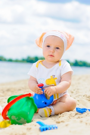 cute baby girl playing on the beach with sand. photo