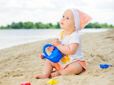 babies with toys: baby girl playing on the beach with sand.