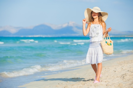 Adorable girl wearing elegant hat on the beach photo