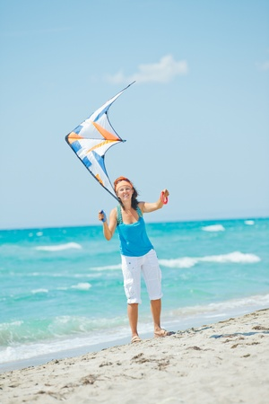 Woman on beach playing with a colorful kite photo