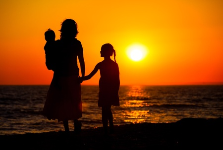 holding mother's hand: Mother and her kids silhouettes