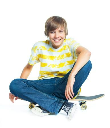 ni�o en patines: el muchacho rubio que se sienta en patineta