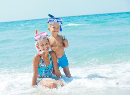 hermanos jugando: Happy Divers En Una Playa Foto de archivo