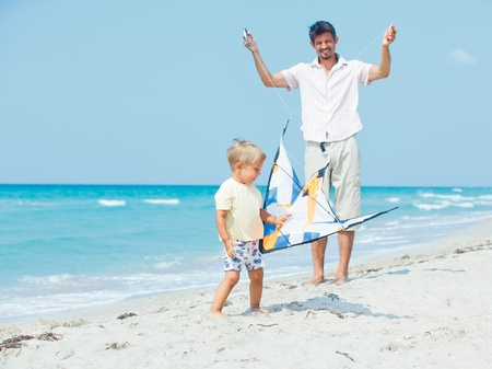 boy with father on beach playing with a kite photo