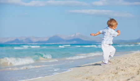 kids playing beach: Young cute boy playing happily at pretty beach