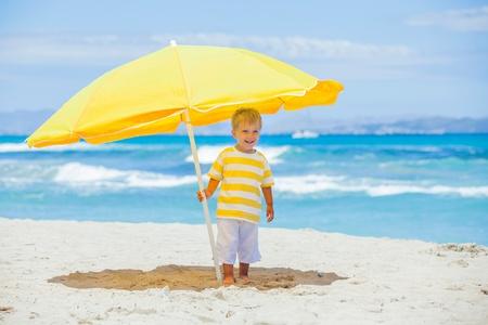 Boy with big umbrella on tropical beach photo