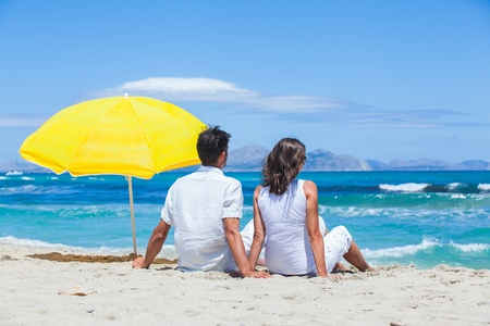 30 to 35: Couple sitting together on the beach