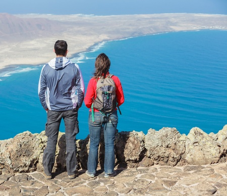 Sport couple standing on cliffs edge photo