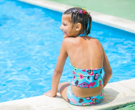 Pretty young girl at pools edge photo