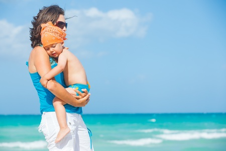 Cute little boy and his mother at beach photo
