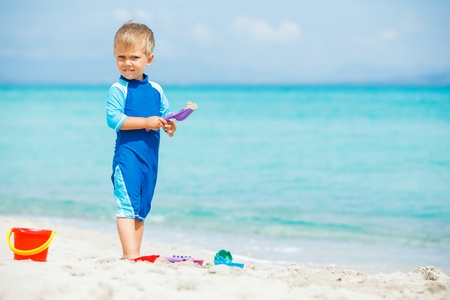 Boy playing with beach toys on tropical beach photo