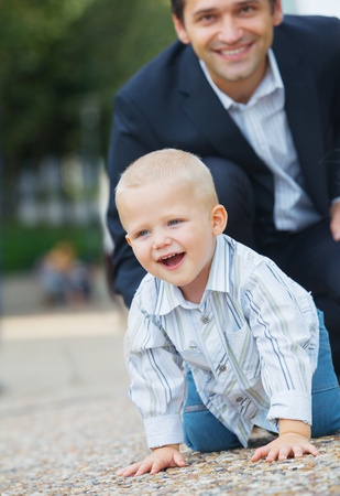 Boy walking in city park with his father photo