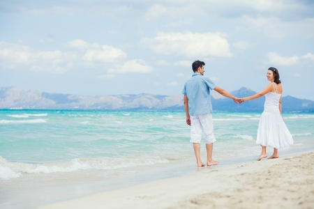 destination wedding: Happy young couple walking on a tropical beach