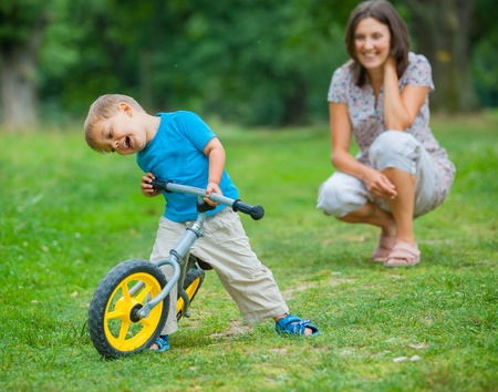 Little boy on a bicycle and his mother watches in the background photo