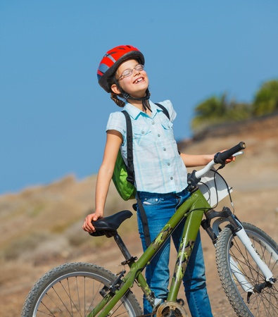 Teenager girl over a bicycle and looking the view photo