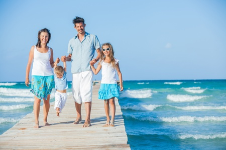 Family of four on jetty by the ocean Stock Photo - 12696610