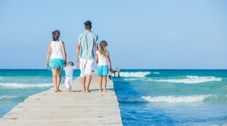 Family of four on wooden jetty by the ocean Stock Photo - 12695959
