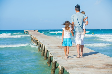Family of three on jetty by the ocean photo