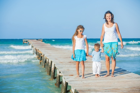 Family of three on jetty by the ocean Stock Photo - 12696655