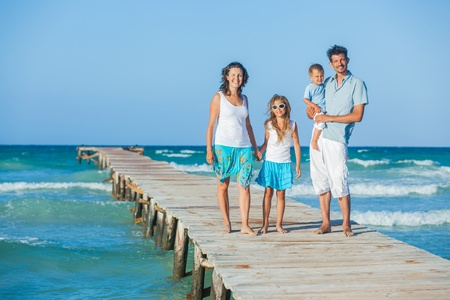 Family of four on jetty by the ocean Stock Photo - 12696650
