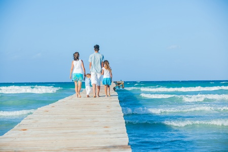 Family of four on wooden jetty by the ocean Stock Photo - 12696646