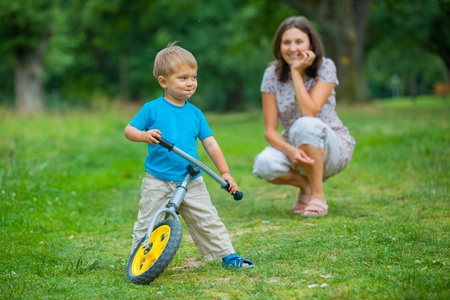 Little boy on a bicycle and his mother photo