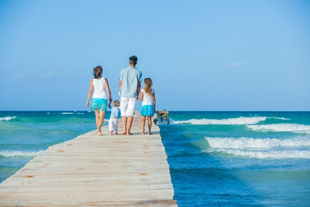 Family of four on wooden jetty by the ocean Stock Photo - 12761063