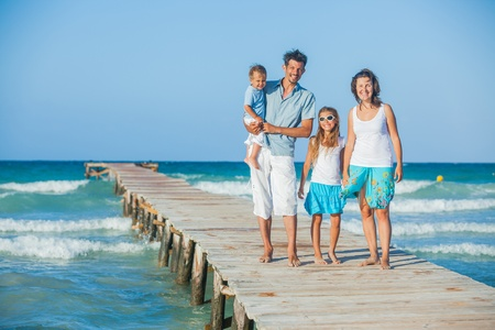 Family of four on jetty by the ocean Stock Photo - 12761215