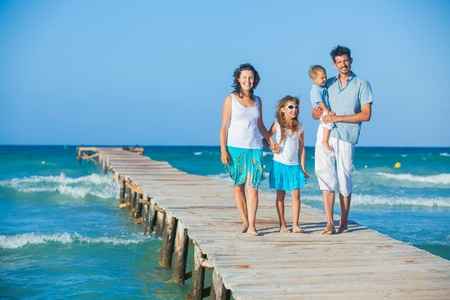 family vacation: Family of four on jetty by the ocean
