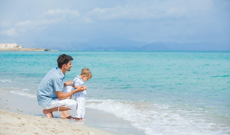 Happy father and his son playing at beach photo