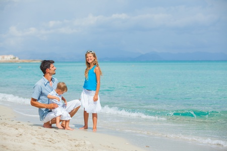 Father with her two kids on beach vacation photo