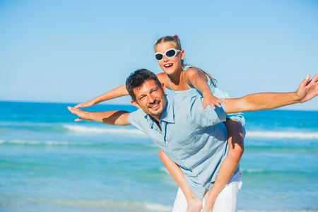 Father and his daughter having fun on beach photo