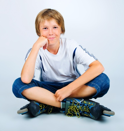 Portrait of young beautiful boy roller skating photo