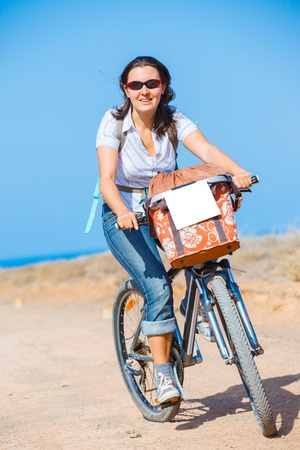 Woman on bike outdoors smiling photo