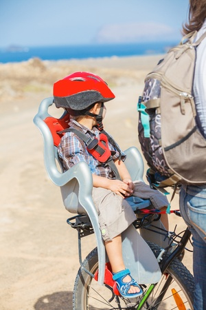 child sitting by bicycle in crash helmet photo
