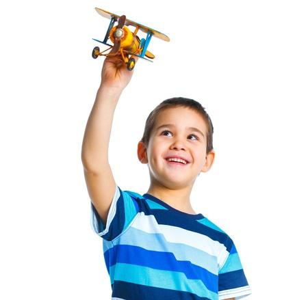 Netter kleiner Junge spielt mit einem Spielzeug-Flugzeug