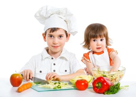 Twee lachende kinderen het mengen van salade