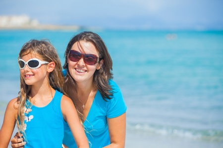 Mother and her daughter having fun on beach photo