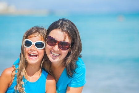 glasses in the sand: Mother and her daughter having fun on beach